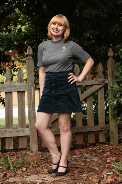 gray, figure-hugging t-shirt with half sleeves and black mini skirt