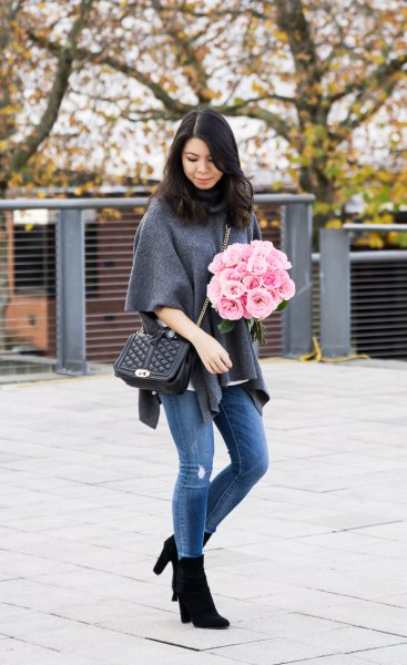 gray poncho sweater with half sleeves, blue jeans and black boots