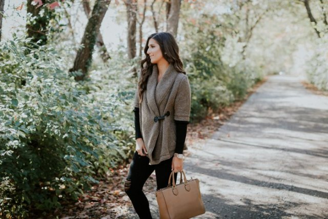 gray half-sleeved sweater with black long-sleeved shirt and brown leather bag