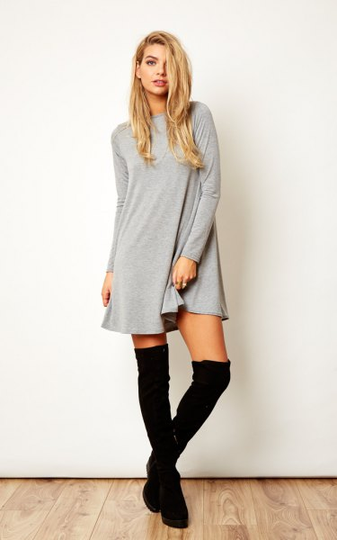 gray long-sleeved swing dress with black over-the-knee boots
