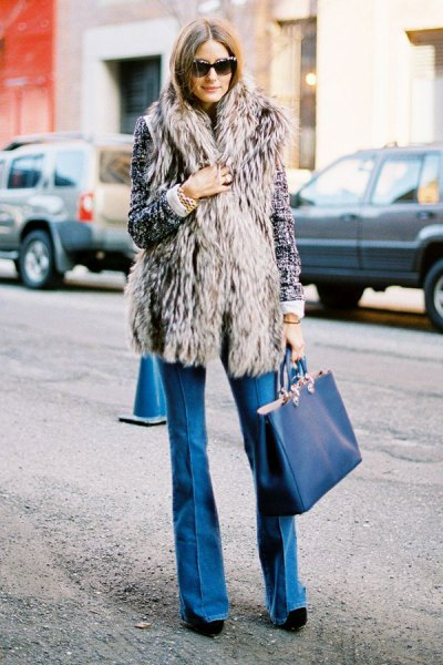 gray long vest with blue flared jeans and dark blue handbag