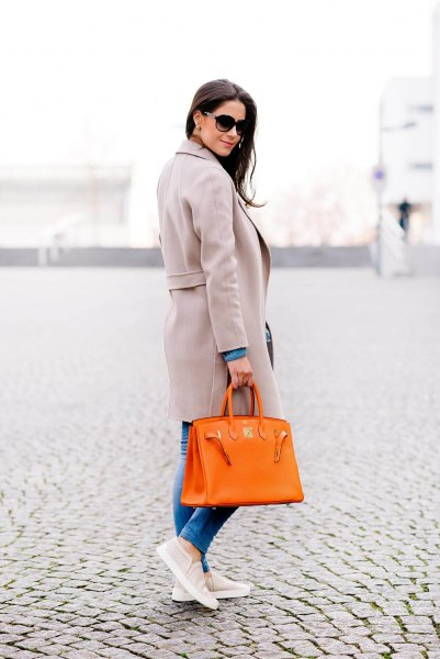 gray long wool coat with blue jeans and canvas shoes