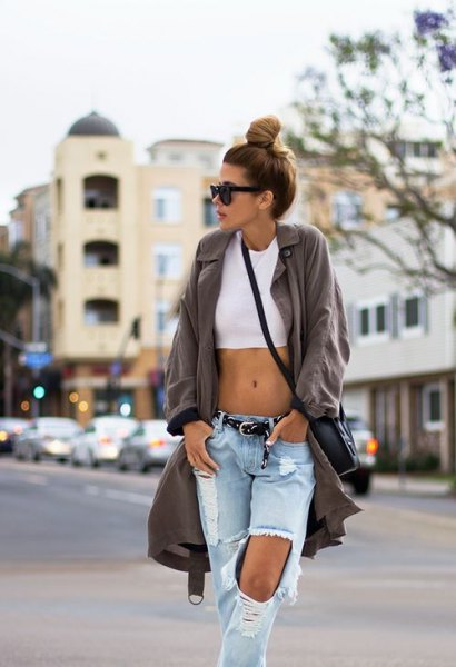 gray longline trench coat with white crop top and ripped baggy jeans