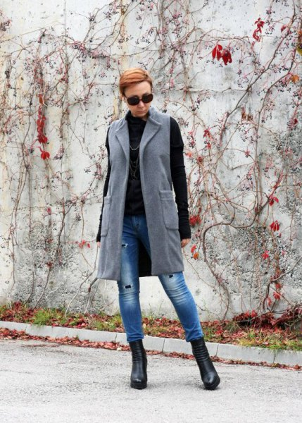 gray longline wool vest with blue skinny jeans and black sweater