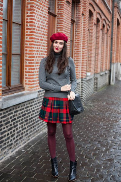 gray sweater with stand-up collar and red and blue plaid pleated skirt