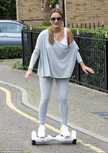 gray one-shoulder cape sweater, white tank top and sneakers