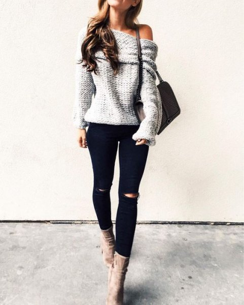 gray knitted sweater with one shoulder and gray suede boots