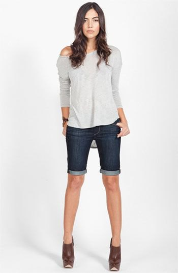 gray long-sleeved T-shirt with one shoulder and dark blue, knee-length stretch shorts