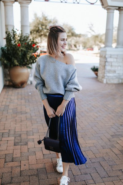 gray one-shoulder sweater with dark blue pleated midi skirt