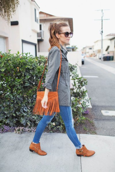 gray parka jacket with blue skinny jeans and suede bag with camel shoulder