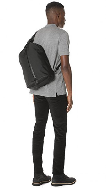 gray polo shirt with black skinny jeans and shoulder bag