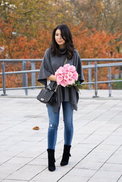gray poncho sweater with blue skinny jeans and black boots