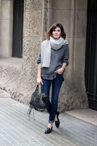 gray, ribbed, thick sweater with dark jeans with cuffs and slip-on slippers made of leather