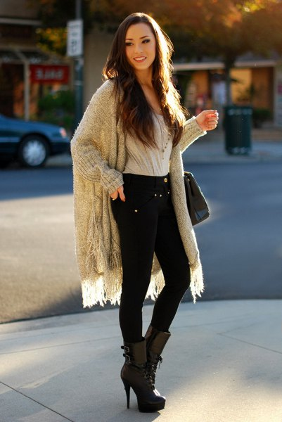 gray, ribbed longline fringe sweater with black skinny jeans and boots with high heels and medium calves