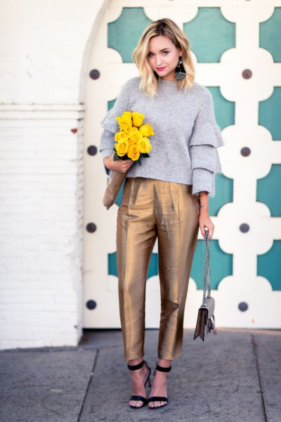 gray crew neck sweater with ruffled sleeves and gold high-waisted chinos