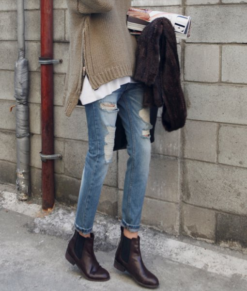 gray side slit sweater with ripped jeans and black leather boots with zippers