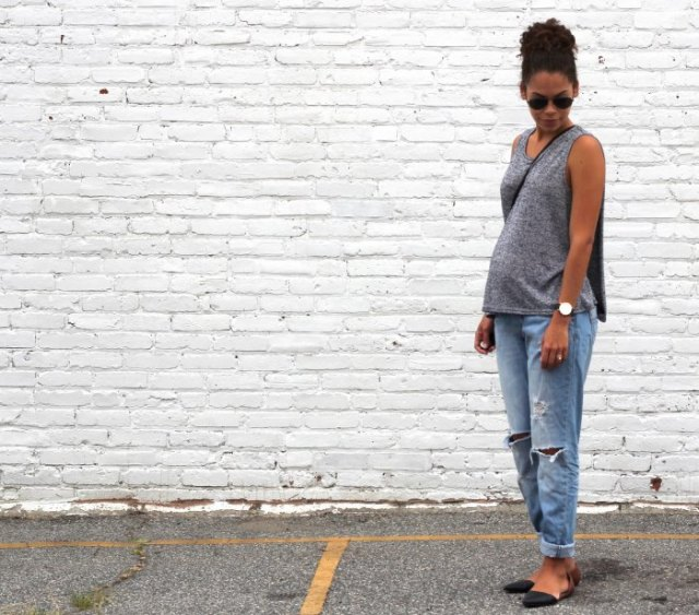 gray sleeveless sweater with scoop neckline and relaxed light blue jeans