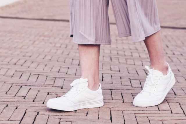 gray striped pants made of chiffon with wide legs and white sneakers