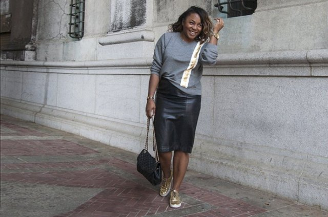 gray sweater with black midi leather skirt and gold low-top sneakers