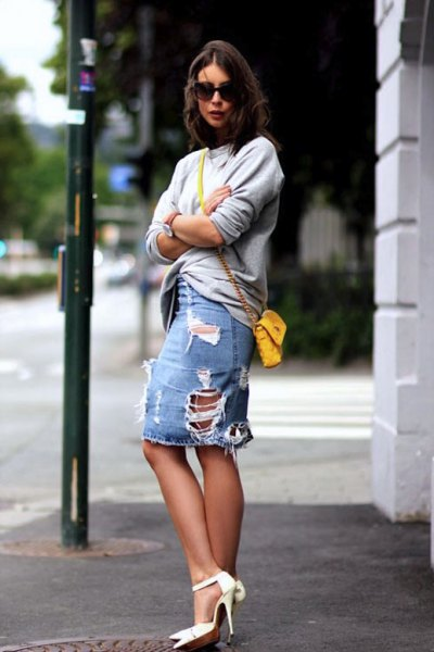 gray sweater with a heavily torn denim skirt