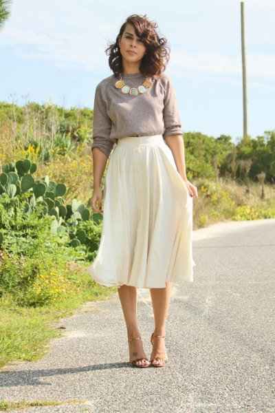 gray sweater with statement chain with white, flowing midi skirt