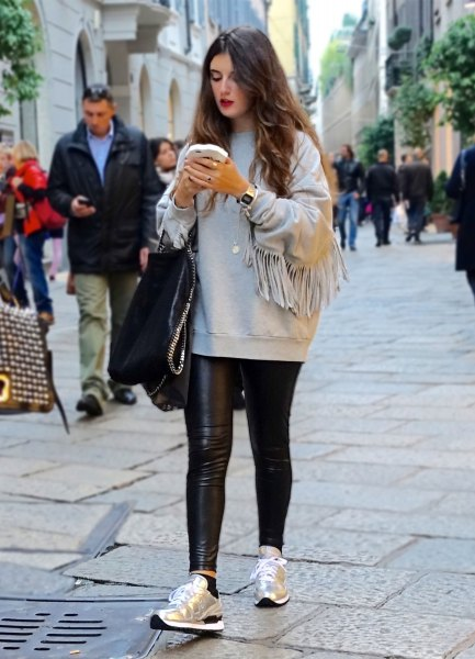 gray sweatshirt with black, narrow leather pants and gold running shoes