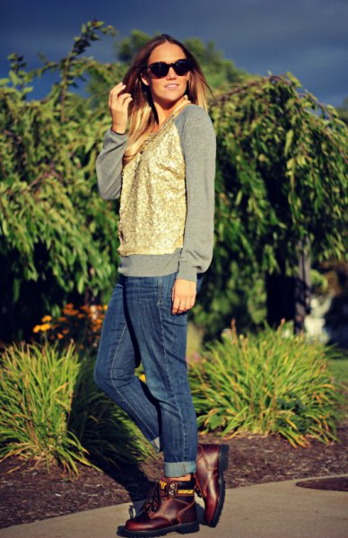 gray sweatshirt with gold vest and blue jeans with cuff