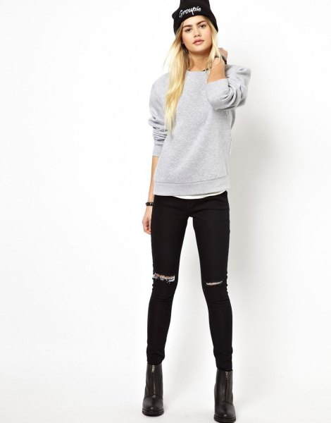 gray sweatshirt with ripped black skinny jeans and knitted hat