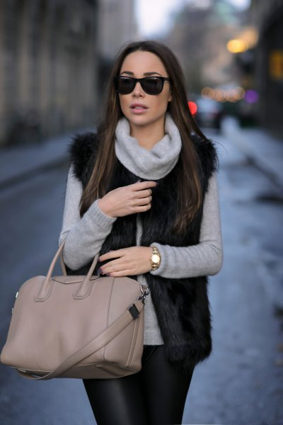 gray turtleneck with black faux fur vest and leather gaiters