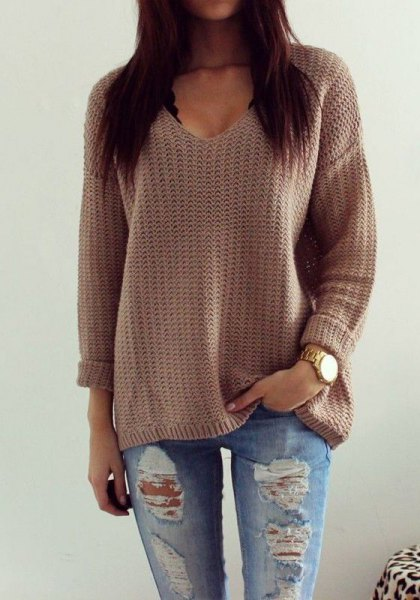 gray knitted sweater with a relaxed fit and V-neckline and torn boyfriend jeans