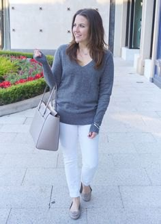 gray sweater with V-neck and white slim fit jeans