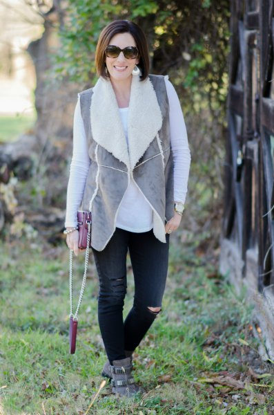 gray vest with black jeans and suede boots