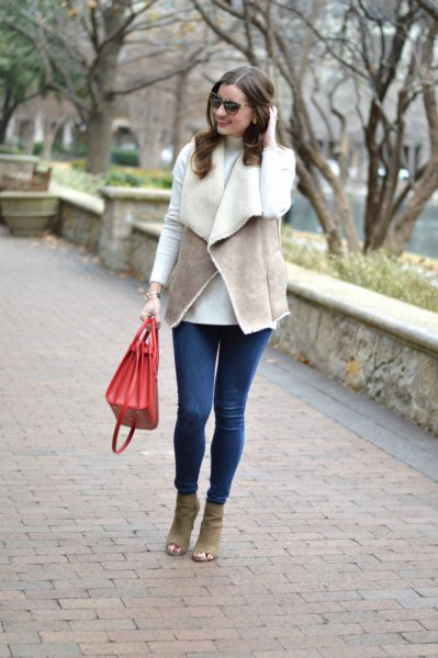 gray vest with white T-shirt and blue skinny jeans