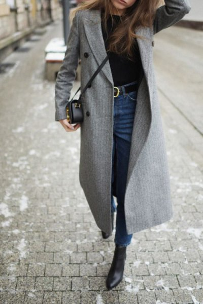gray walker coat with blue skinny jeans with a high belt