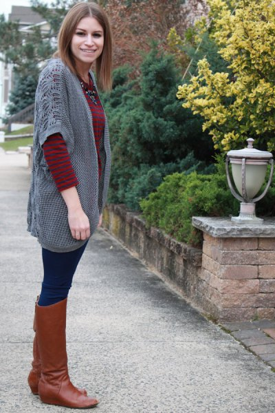gray cardigan with wide sleeves and knee-high boots made of brown leather