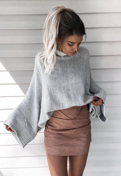 gray knitted sweater with wide sleeves and matching matt leather skirt