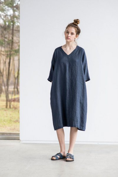 gray tunic dress made of linen with wide sleeves and black slide sandals