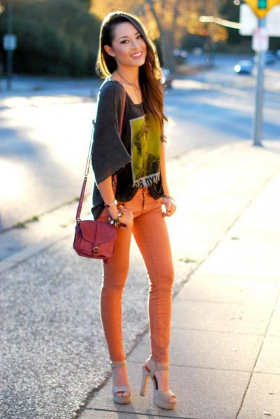 gray t-shirt with wide sleeves and orange skinny jeans