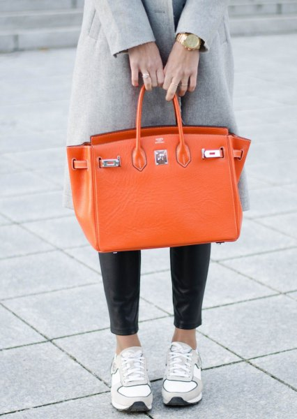 gray wool coat with black leggings and orange leather handbag
