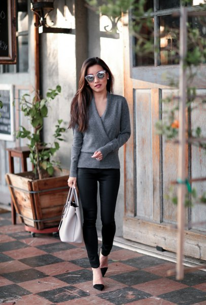 gray wrap sweater with black coated skinny jeans
