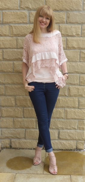 Blush blouse with half-sleeved lace neckline and dark blue skinny jeans with cuffs