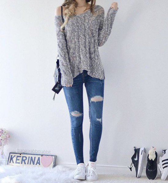 heather gray knit sweater with one shoulder and blue skinny jeans