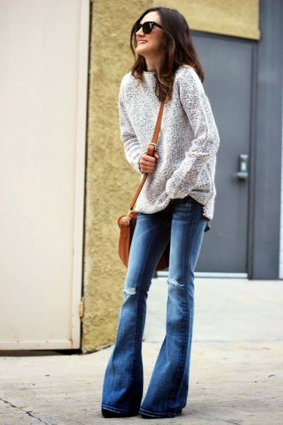 heather gray sweater with blue torn flared jeans