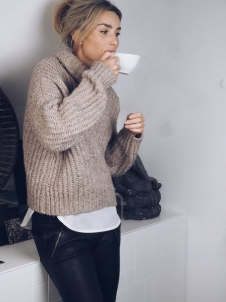 gray, chunky sweater with a high neck, black leather pants