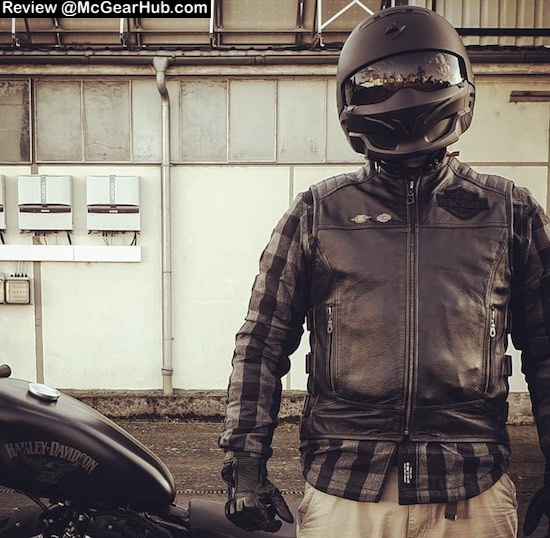 A photograph showing a Harley rider wearing a leather biker vest .