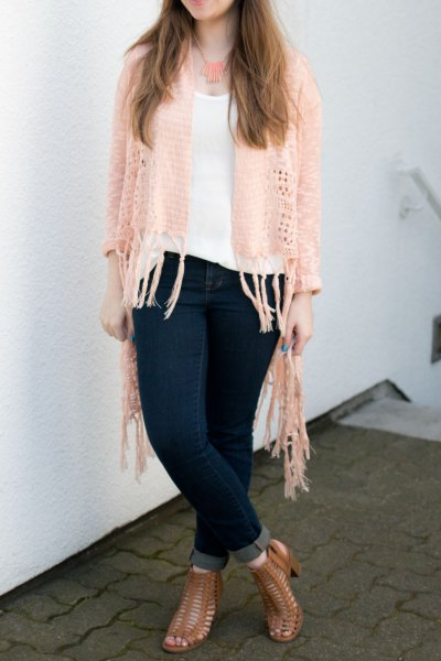 Crochet cardigan with ivory fringes, white top with a scoop neckline and dark blue skinny jeans