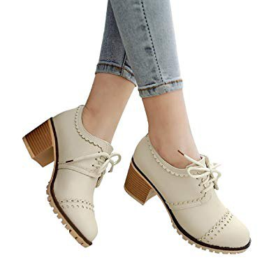 Wing-tip shoes with ivory heels and light blue skinny jeans