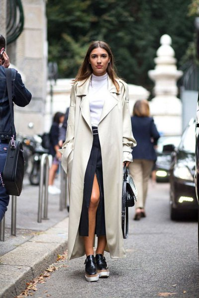 Ivory maxi trench coat with white mock neck sweater and black high split skirt