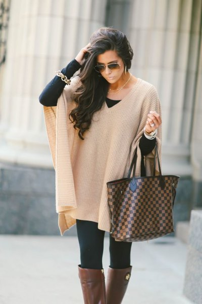 Ivory ribbed cape sweater with black leggings and gray over-the-knee boots