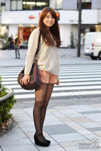 Ivory ribbed sweater with a relaxed fit, light orange mini-shorts and patterned tights